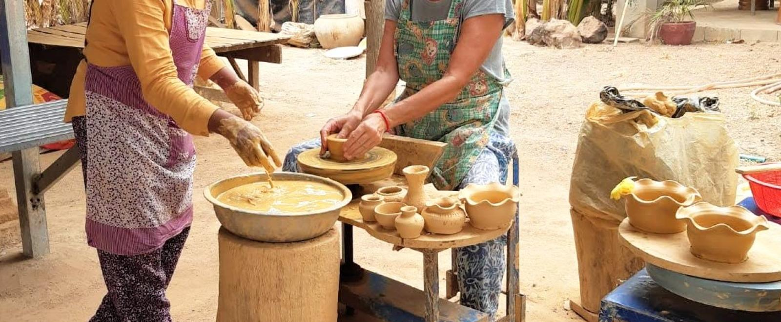 An older volunteer participates in a pottery class as part of her Khmer cultural experience in Cambodia.